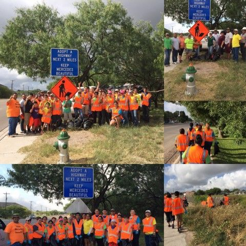 volunteers in orange vest posing with adopt a highway sign