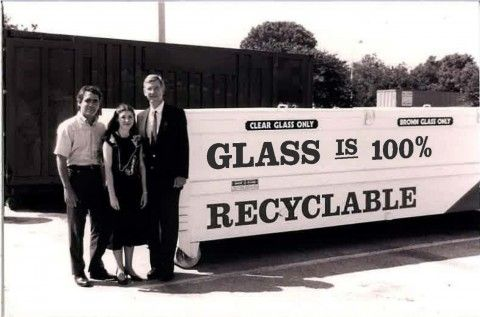 Photo taken in 1990 of 1 woman and 2 men standing in front of a glass recycling receptacle