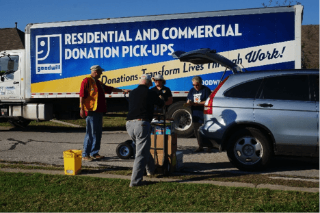 Large goodwill truck and group of people loading up a car with donations