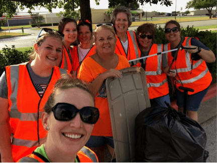 Group of women in orange vests, ready to pick up trash